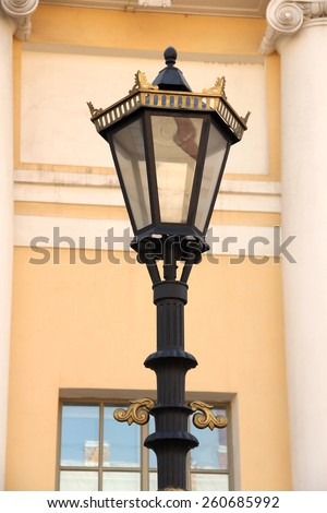 Black with gold street lamp standing in front of beige wall with pillars - stock photo