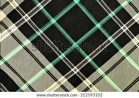 Black with white and green plaid print as background. Scottish tartan pattern. Symmetric rhombus pattern.