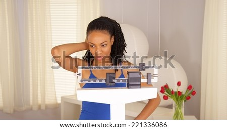 Black woman disappointed after checking weight - stock photo