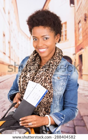 Black woman in casual clothing and bag ready to travel with tickets concept transport airplane airline bus train traveling airport counter depart flight - stock photo