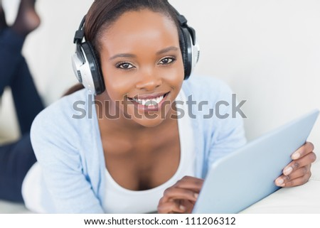 Black woman listening music while looking at camera in a living room