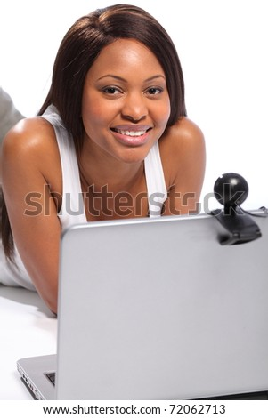 Black woman lying on floor keeping in touch with friends on laptop and webcam - stock photo