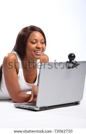 Black woman lying on floor using laptop and web cam - stock photo