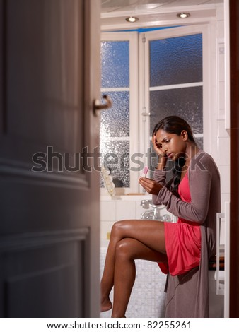 black woman with pregnancy test in bathroom, getting bad news. Vertical shape - stock photo