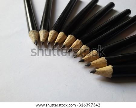 black wooden pencils on soft white background - stock photo