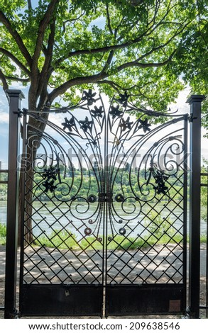 black wrought iron gate in the forefront with tree and hills and lake in the background in the summer under a blue sky. - stock photo