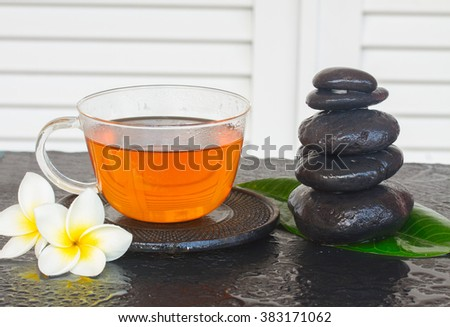 black zen stones with cup of tea and flowers - stock photo