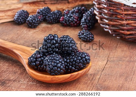 Blackberries in a spoon on wooden background - stock photo