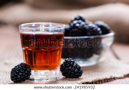 Blackberry Liqueur in a shot glass (on rustic wooden background)  - stock photo