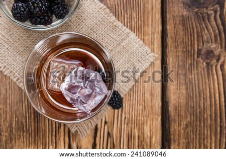Blackberry Liqueur shot (with some fresh fruits) on wooden background