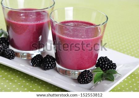 Blackberry smoothie with fresh blackberries on green background