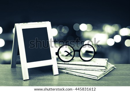 blackboard and glasses on books with bokeh light in city night time background - stock photo