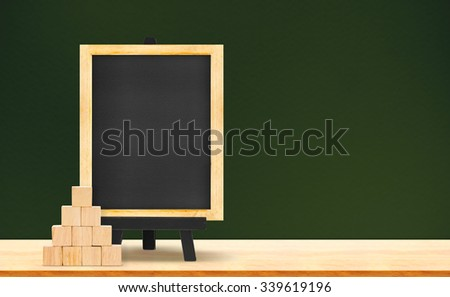 Blackboard and wood cube on wood table on dark green background,Mock up for adding your text