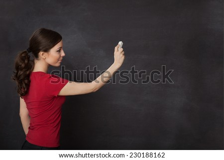Blackboard / chalkboard. Woman writing with copyspace for text - stock photo