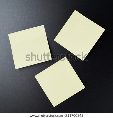 Blackboard covered with three copyspace empty sticky paper notes - stock photo