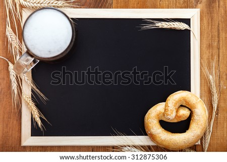Blackboard for the menu, you can write with chalk. Original bavarian Oktoberfest background.  Glass of beer on wooden background with hops, wheat and Pretzel. Mug of beer festival template background. - stock photo