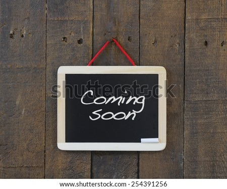 Blackboard hanging on a old wooden wall with phrase Coming soon. - stock photo