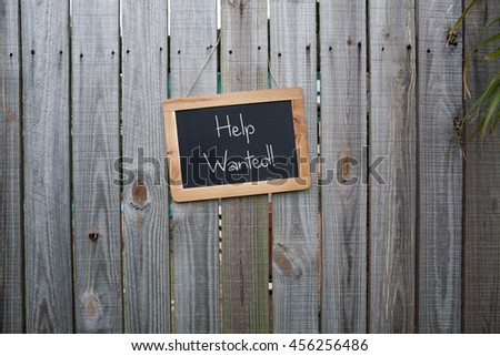 Blackboard help wanted sign on wooden fence - stock photo