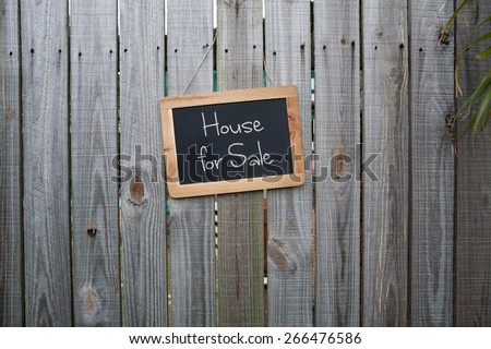 Blackboard home for sale sign on wooden fence - stock photo