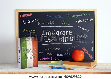 Blackboard in an Italian language classroom with the message Learn Italian and some other linguistic words. - stock photo
