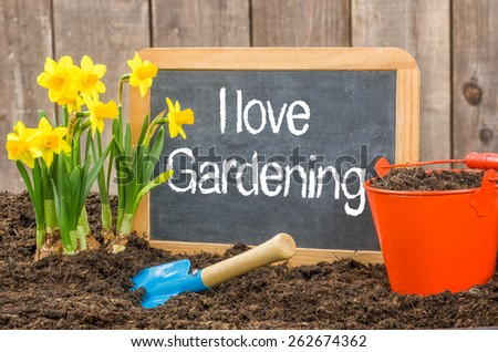 Blackboard in the flower bed with the text I love gardening - stock photo