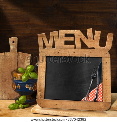 Blackboard Menu in the Kitchen / Empty blackboard with wooden frame and text Menu in the kitchen with mortar and pestle with basil leaves and cutting boards. Template for food menu - stock photo