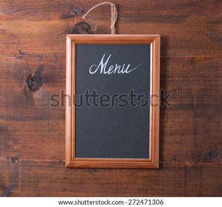 Blackboard on wooden surface - stock photo