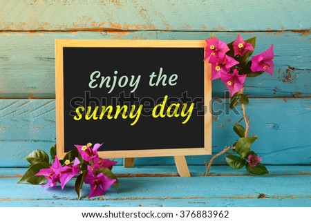 blackboard over blue wooden shelf with the phrase ENJOY THE SUNNY DAY.  - stock photo
