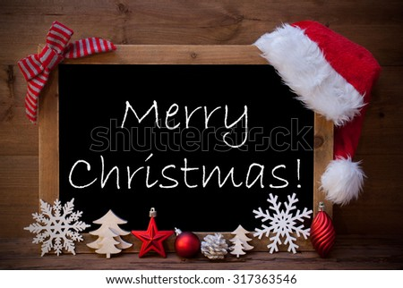 Blackboard With Red Santa Hat And Christmas Decoration like Snowflake, Tree, Christmas Ball, Fir Cone, Star. English Text Merry Christmas. Brown Wooden Background - stock photo