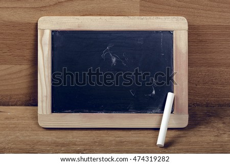 Blackboard with text that stands on the old wooden table