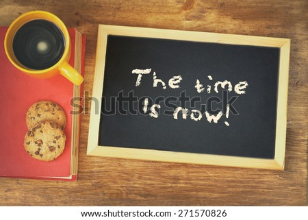 blackboard with the phrase the time is now written on it, next to coffee cup and cookies - stock photo