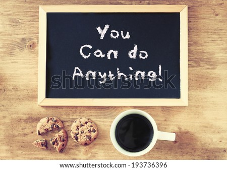 blackboard with the phrase you can do anything over wooden background with cup of coffee and cookies - stock photo