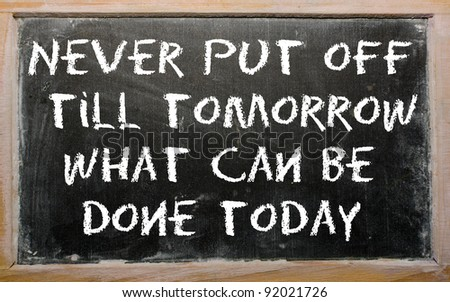 """Blackboard writings """"Never put off till tomorrow what can be done today"""" - stock photo"""