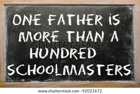 "Blackboard writings ""One father is more than a hundred schoolmasters"" - stock photo"