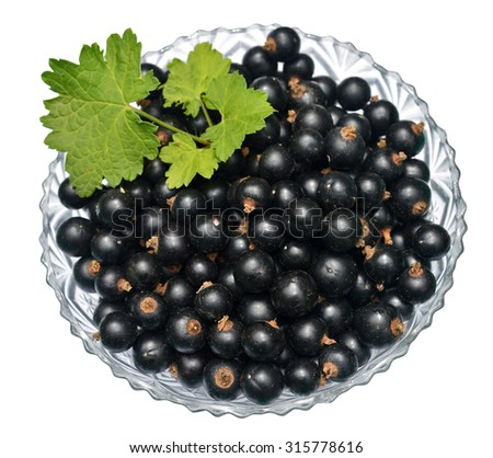 Blackcurrant with leaves in glass bowl - stock photo