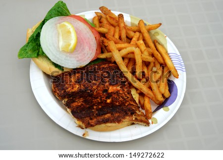 blackened mahi mahi fish sandwich and a french fries on a plate - stock photo