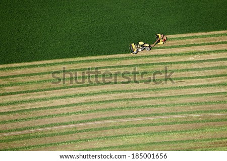 Blackfoot, Idaho, USA Aug. 7, 2012 An aerial view of farm machinery harvesting hay in an alfalfa field