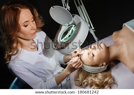 Blackhead cleansing on woman face during facial treatment at beauty clinic - stock photo
