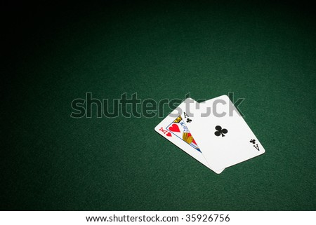 Blackjack hand on green baize table ace and king - stock photo