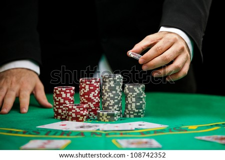 blackjack in a casino, a man makes a bet, and puts a chip - stock photo