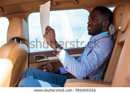 Blackman in a blue shirt sits on car's back seat. - stock photo