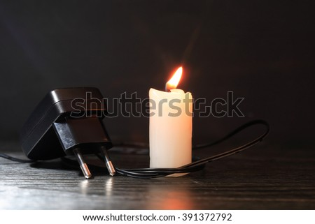 Blackout concept. Electric charger with cable near lighting candle on dark background - stock photo