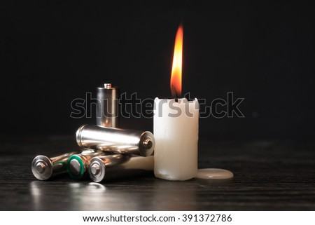 Blackout concept. Few batteries near lighting candle on dark background - stock photo