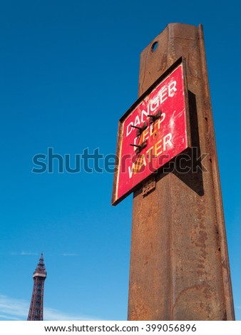 Blackpool, England, 05/05/2015, Danger deep water warning hazard sign on a rusty metal beam, with blackpool tower in the background