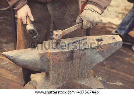 Blacksmith forges a horseshoe in a smithy - stock photo
