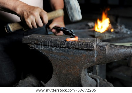blacksmith forges iron in the forge - stock photo