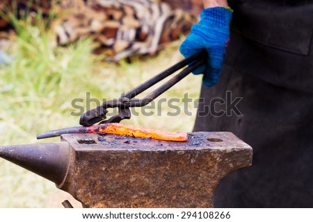 Blacksmith lays down a hot iron on anvil for forging - stock photo
