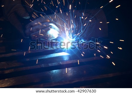 Blacksmith working on decorative handrail using welding equipment making beautiful blue light from torch - stock photo