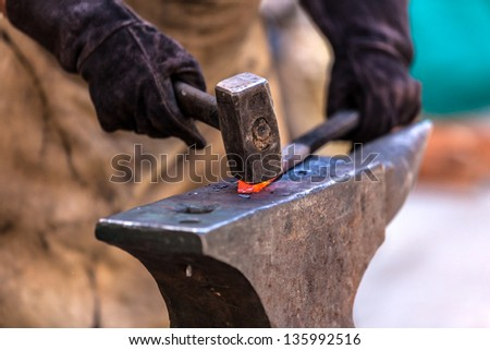 Blacksmith working on metal on anvil at forge detail shot - stock photo