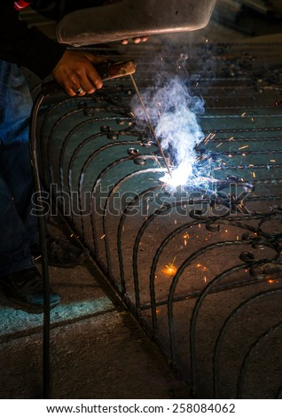 Blacksmith working on wrought iron using welding equipment making beautiful blue light from torch
